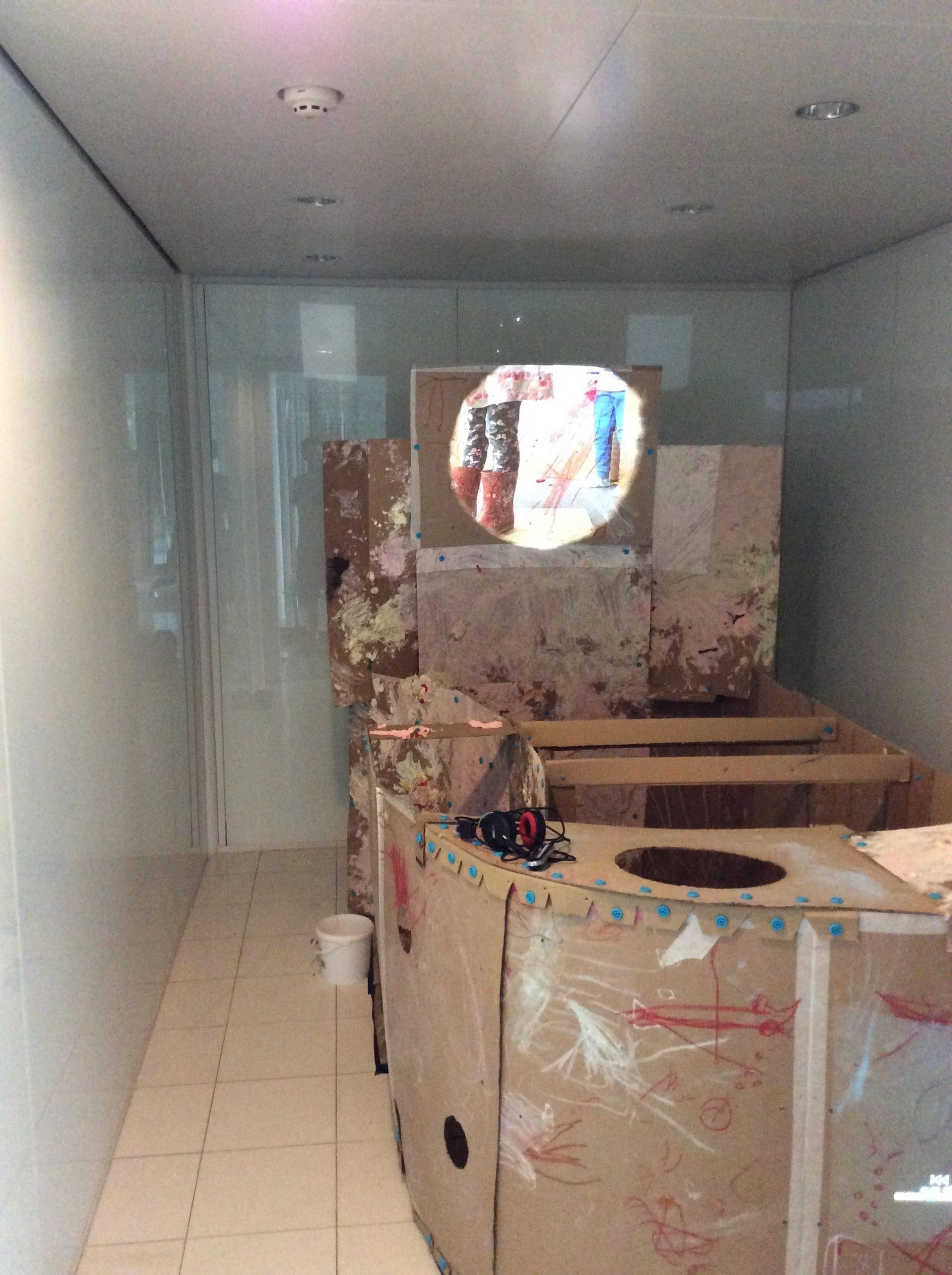 cardboard, white walls, projected legs in wellies