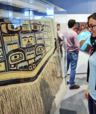 Women looking at Sonny Assu Exhibit