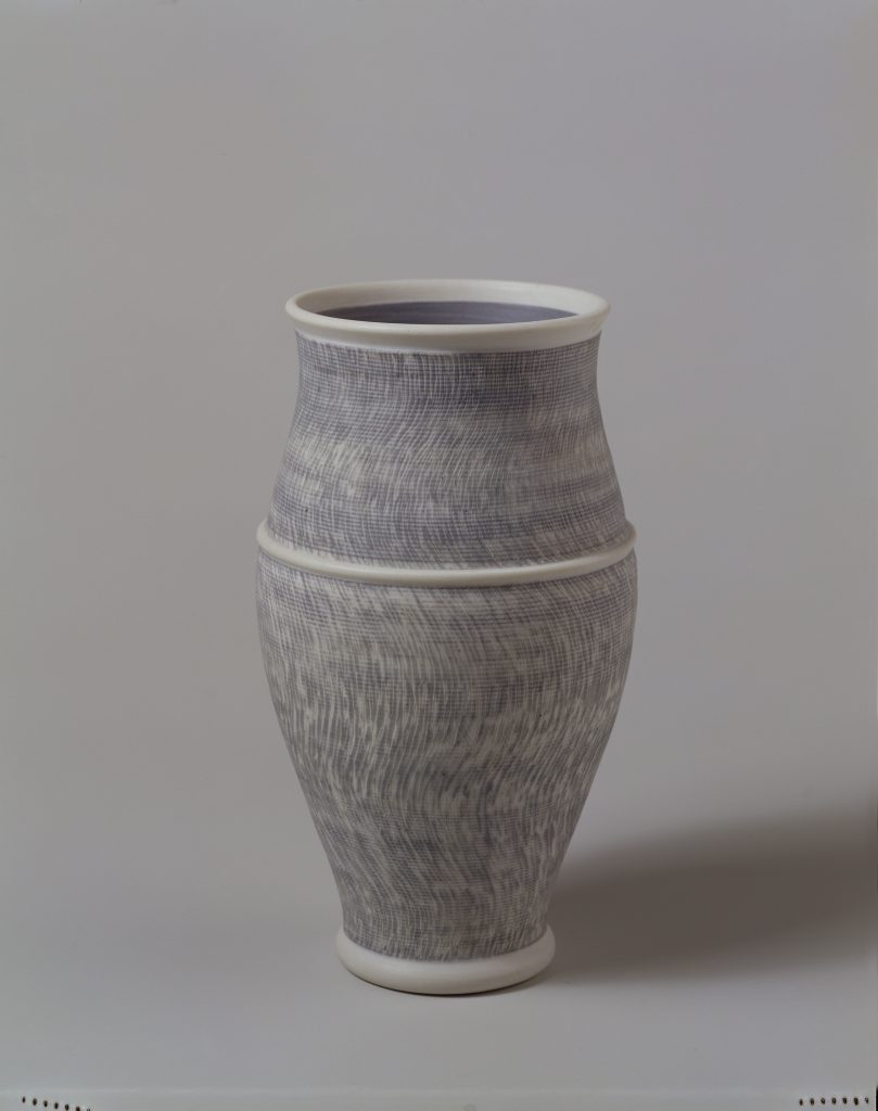 A white vase by Julian Stair crossed with blue lines