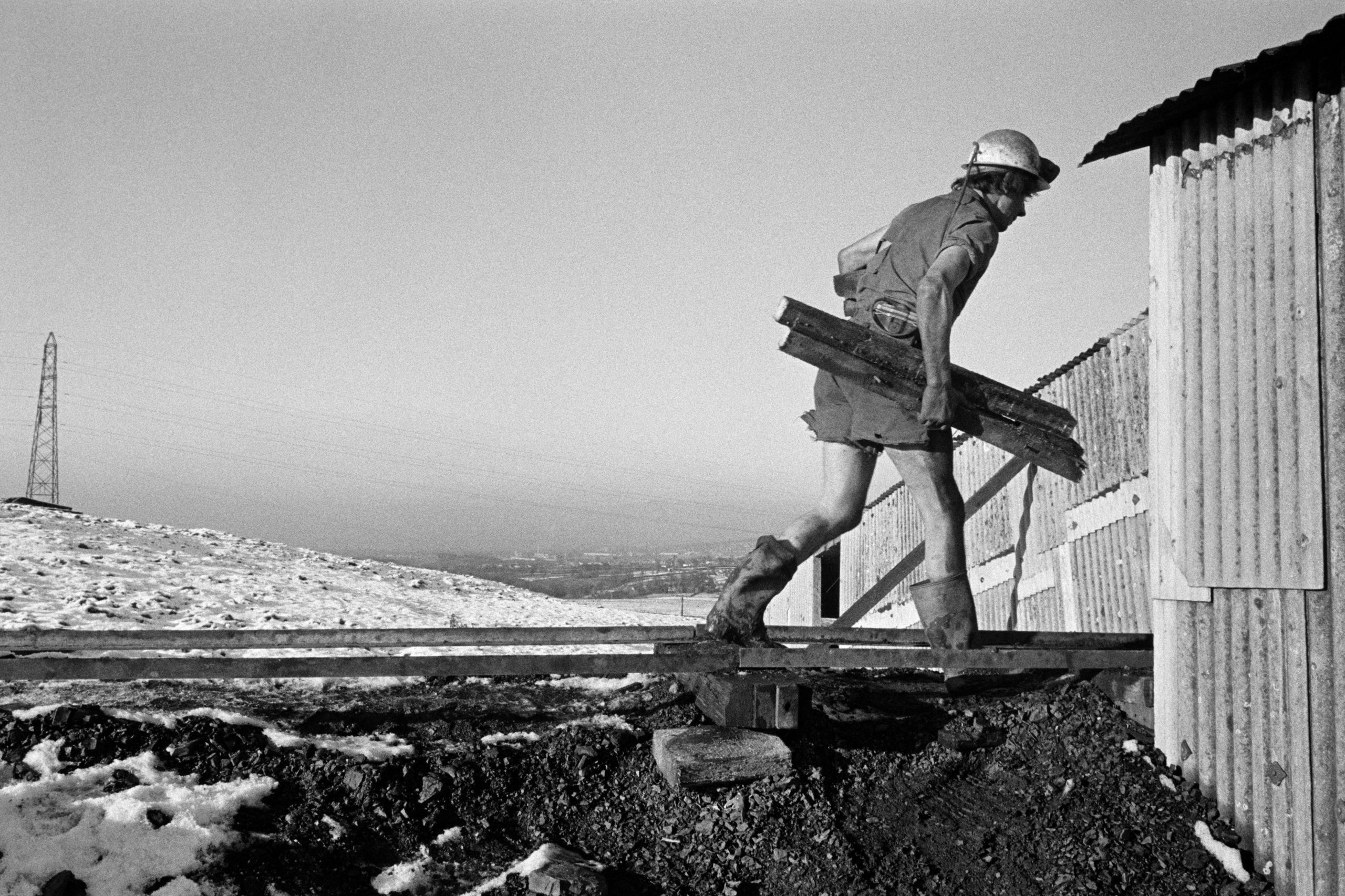 A black and white photograph of a miner carrying wood