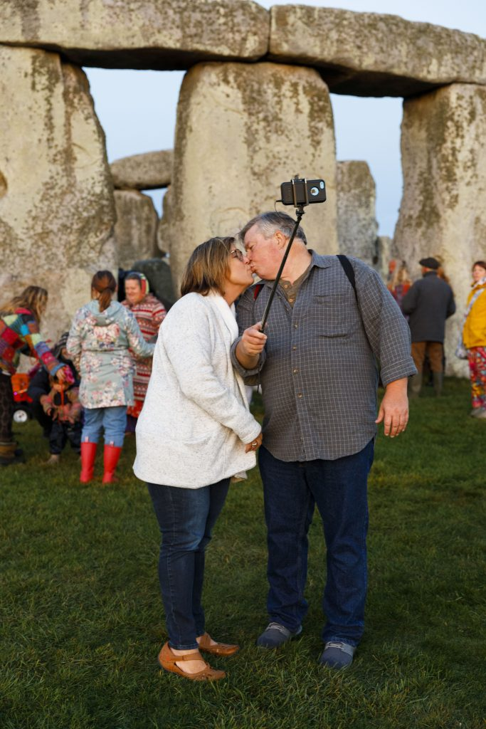 Photograph of a couple kissing in front of the historical site of Stongehenge, United Kingdom