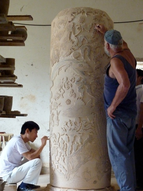 Photograph of Spitting Image co-creator Roger Law and his collaborator Mr Wu Song Ming carving a large pot