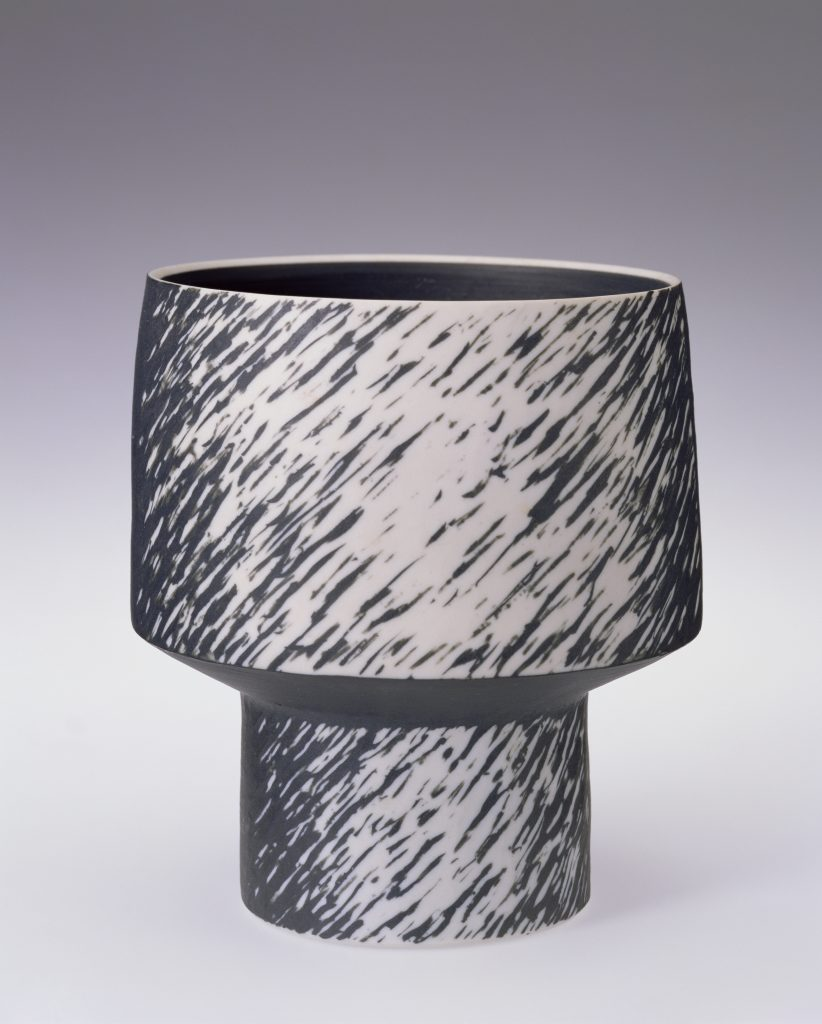 A black and white footed porcelain pot by ceramic artist Julian Stair, featuring sgraffito decoration