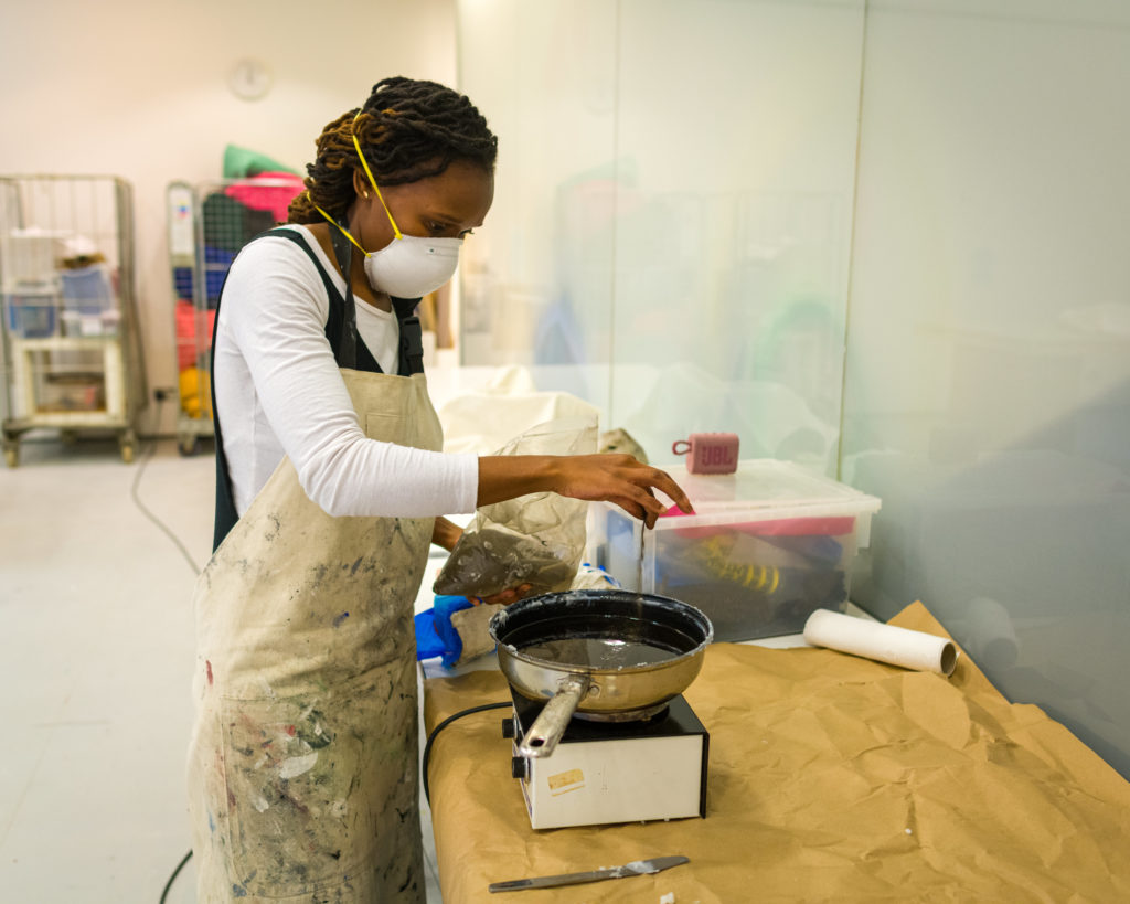 Photograph of South African artist Sethembile Msezane preparing an artwork