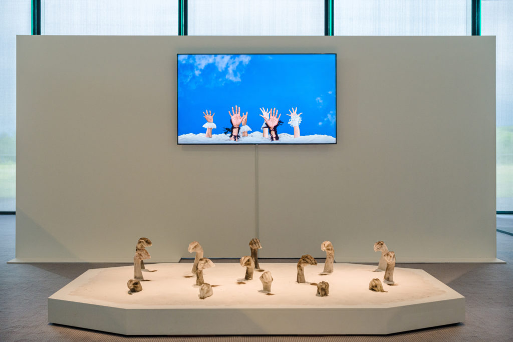 Installation view from the exhibition Sethembile Msezane: Nibizwa Ngabangcwele, featuring video art on a television screen and wax sculptures in the shape of hands